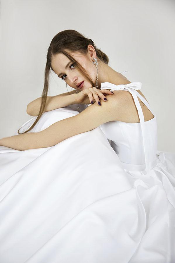 Svatební šaty zdobené bílou mašlí